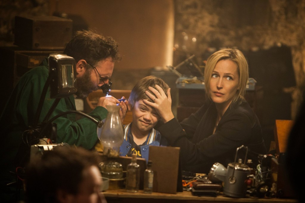Donald (David McSavage) performs a delicate procedure on Connor (Milo Parker), assisted by Kate (GIllian Anderson) in a scene from Robot Overlords. © MEDIATOR 452 LIMITED/BRITISH FILM INSTITUTE 2014