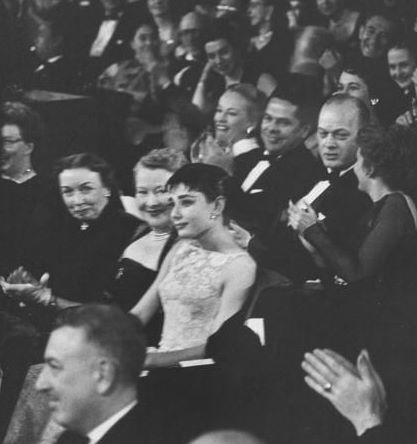 March 25th, 1954, the oscar night. Near tears after her name was called as the winner, Audrey sits for a moment as the audience applauds her.