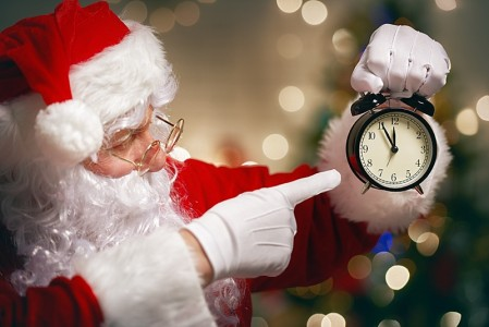 Portrait of Santa Claus with alarm clock in hand