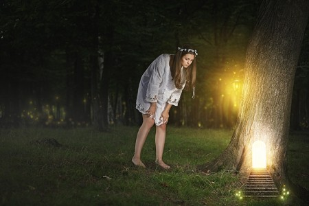 Beautiful young woman finds the door to fairy realm . Fantasy concept